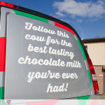 A photo of the rear windows of the Mama Fuscos van displaying one of their taglines. Follow this cow for the best tasting chocolate milk you've ever had!