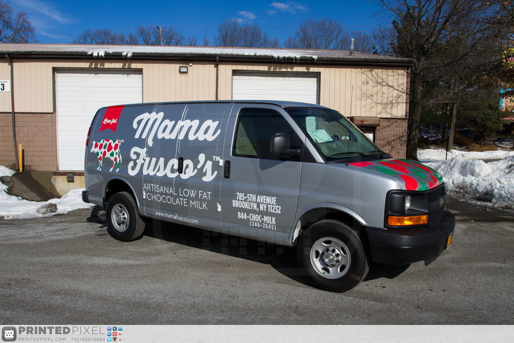 A wide angle 3/4 view photo of Mama Fuscos van all wrapped with piles of snow in the background.