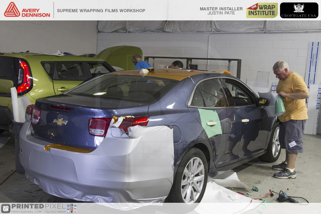 Avery Dennison Supreme Wrapping Films Workshop demo vehicles covered in different colors of vinyl.