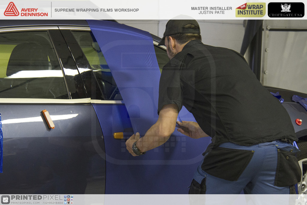 Justin Pate stretching Supreme Wrapping film over the vehicle.