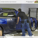 Avery Dennison Night Blue Metallic Supreme Wrapping film being installed on the passenger door of the demo vehicle.