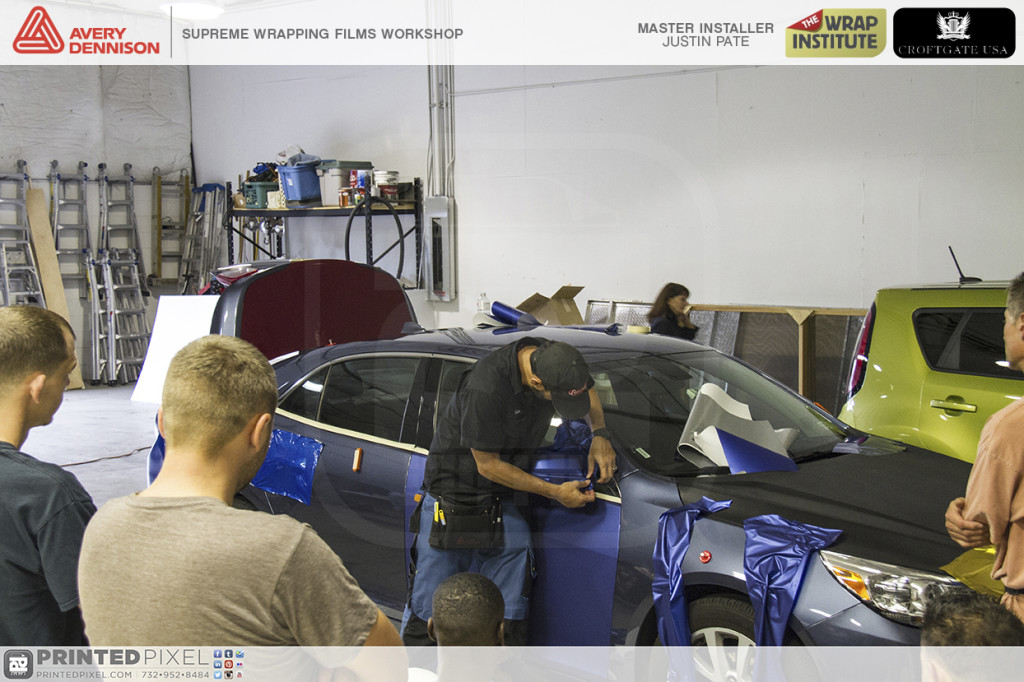Justin Pate heating blue vinyl over a mirror during Avery Dennison Supreme Wrapping Films Workshop.