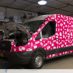 Claim it Ford Transit sampling vehicle fully wrapped. Front view with hood open..