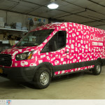 Claim it Ford Transit sampling vehicle fully wrapped. Front driver view.