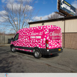 Claim it Ford Transit sampling vehicle fully wrapped. Driver side rear view.